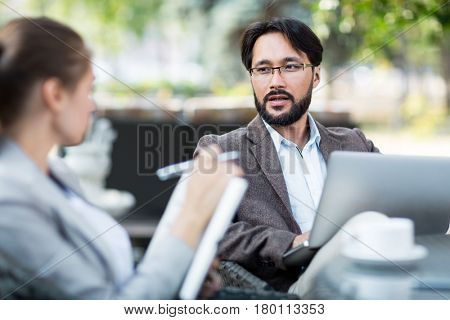 Asian HR manager conducting interview with female applicant for position while sitting in outdoor cafe, waist-up portrait