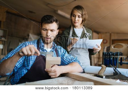 Handsome bearded craftsman measuring width of wooden piece with vernier caliper while his pretty female apprentice taking notes in workshop