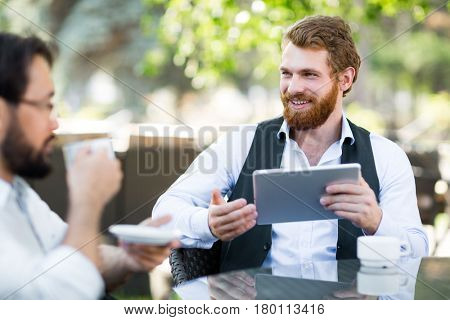 Handsome fair-haired businessman having small talk with his colleague while sitting in small outdoor cafe and drinking fragrant coffee, waist-up portrait