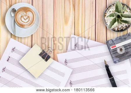 music note paper cactus fountain pen tape cassette and coffee latte on wooden table