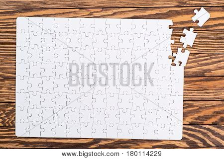 Incomplete white puzzles on the wooden background.