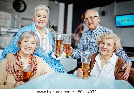 Lovely portrait of two smiling elderly women sitting in comfortable armchairs and looking at camera while their friends sitting on armrests and embracing them slightly