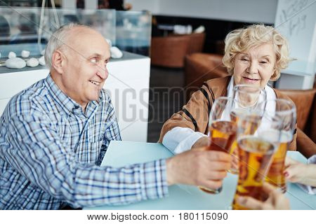 Profile view of handsome senior man looking with toothy smile at his pretty female friend while clanging beer glasses together