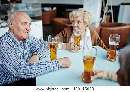 Senior people gathered together in pub and drinking beer while their male friend entertaining them with small talk