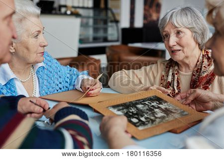 Elderly woman with colorful kerchief on shoulders looking into distance thoughtfully while telling her friends story of her childhood and showing them family photo book