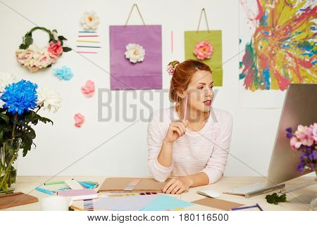 Pretty blond-haired interior designer with pen in hands looking thoughtfully at computer screen while sitting in office decorated with flowers and paintings