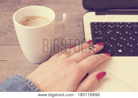 Female Working On Laptop In Cafe. White Mug Of Coffee. Close Up Of A Woman Hand With Rings And Long