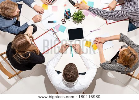 Team sitting behind desk, checking reports, talking. Top View. The business concept of collaboration, team work, meeting