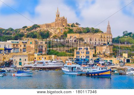 Beautiful cityscape over Gozo island with medieval architecture and passenger boats on the harbor - in Malta