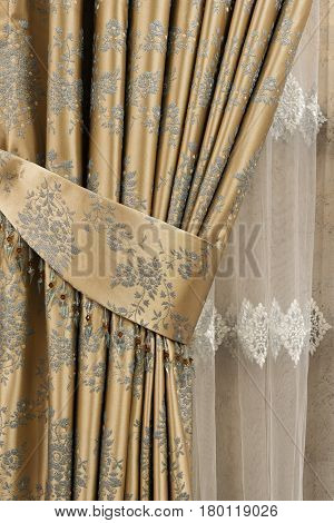 Part Of Beautifully Draped Curtain On The Window In The Room. Close Up Of Piled Curtain. Gold Luxury