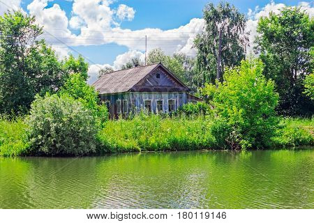 Russian village house on the lake shore on a summer day