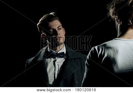 Two handsome men standing opposite on black background. Male model in white tshirt casual wear. Fashion confrontation. businessman in classic bow tie shirt and dark coat.