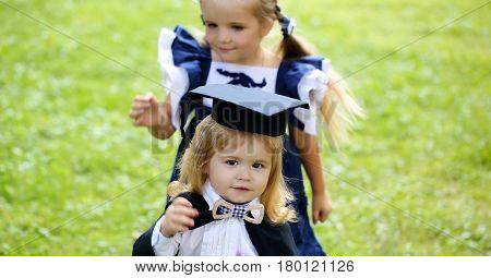 Cute little girl with long hair in blue dress dressing adorable small boy in black graduation hat or cap and robe on summer day outdoors on green grass background