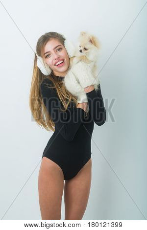 Happy pretty girl or sexy woman with long hair in earmuffs black bodysuit woollen mittens winter fashion smiling with cute pomeranian dog or puppy pet in hands on white background
