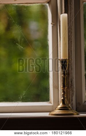 Old vintage objects wood concept. Old vintage window and vertical candle in candlestick