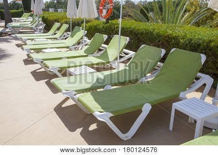 Line of green sunloungers on swimming pool Andalusia Spain