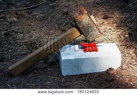 Grotesque fun image - toy small red anvil and huge rusty hammer on white brick against the background of the forest land. Selective focus.