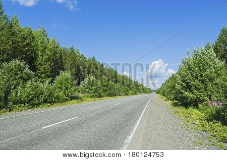 Beautiful summer landscape with a road receding into the distance and the white clouds in the blue sky.