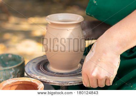 Irshava,Ukraine - October 4.2015. Potter shaping clay jug.