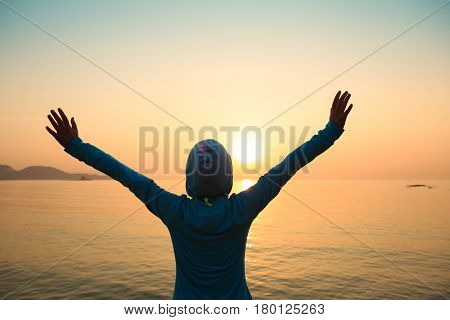 Happy woman with open arms at sunset on beach