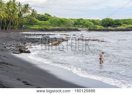 Woman snorkeling in Punalu'u black sand beach, Big Island, Hawaii