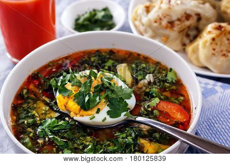 Vegetable soup with egg and greens on a background of tomato juice. Still life. On the surface is a spoon with chopped egg and greens. On the background of a glass of tomato juice, a rosette with herbs and a dish with ravioli
