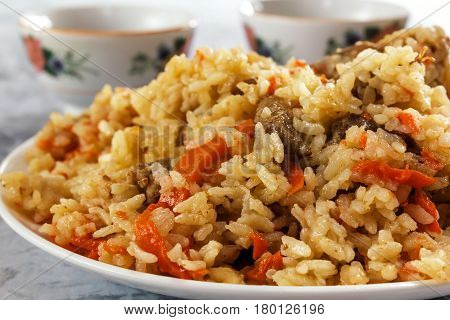 Friable pilaf with meat on a background of cups with tea. Closeup