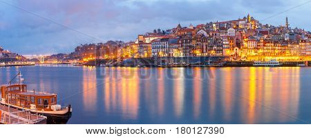 Ribeira and Old town of Porto with mirror reflections in the Douro River during evening blue hour, Portugal, Portugal.