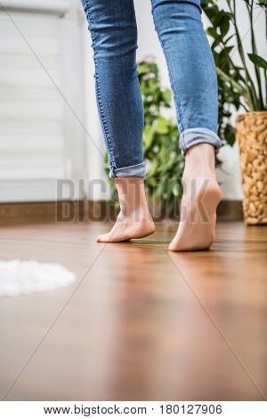 Floor heating. Young woman walking in the house on the warm floor. Gently walked the wooden panels.