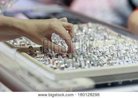 Buyer's hand and counter with jewelry. Sale
