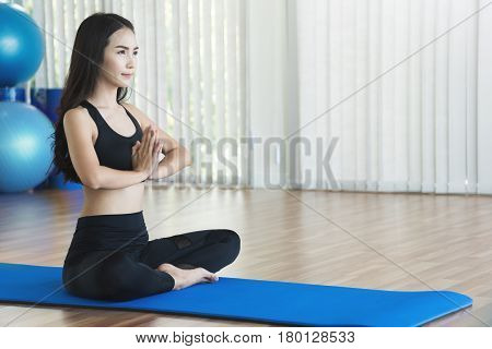 Young Asian woman in prayer position of yoga. Copy space.