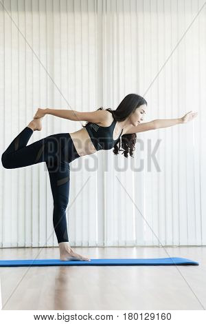 Young Asian woman practicing yoga. Copy space. Happiness smiling.