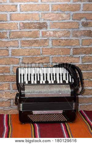 Accordion By The Old Retro Brick Wall