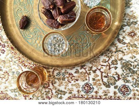 Arabic food and drink. A tray filled with bowl of sweet dates and black tea.