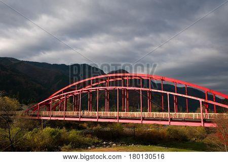 Red bridge in Okuhida onsen autumn season Kyoto Japan.