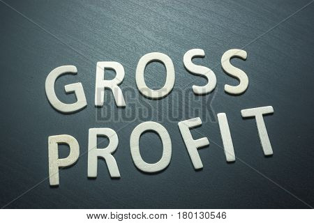 Gross profit written with wooden letters on a green background to understand a concept of economics and finance