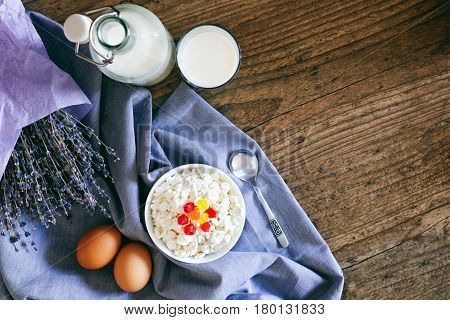 Dairy products on dark wooden table. Sour cream, milk, cheese, egg. Top view with copy space.