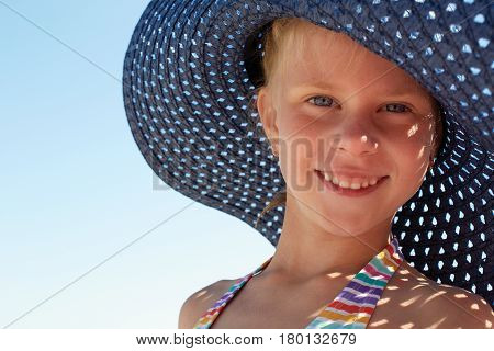 Child in blue hat relaxing on the beach against sea and sky background. Summer vacation and travel concept