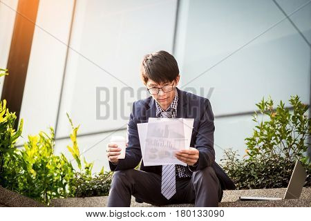 Looking for the right document. Confident young business man in formal wear taking the documents out of briefcase while sitting outdoors.