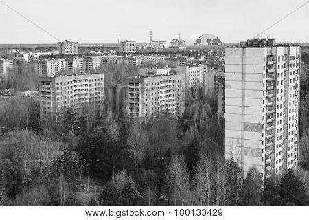 Forgotten city of Pripyat and Chernobyl Nuclear Power Plant sarcophagus in distance