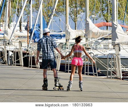 Lausanne Switzerland - August 26 2016: Lausanne Switzerland - August 26 2016: Young couple roller skating at the embankment of Marina on Lake Geneva Lausanne Ouchy fishing village Switzerland