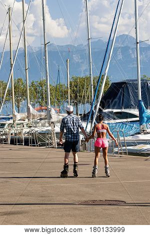 Lausanne Switzerland - August 26 2016: Young couple roller skating at the embankment of Marina on Lake Geneva in Lausanne Ouchy fishing village Switzerland