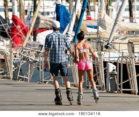 Lausanne Switzerland - August 26 2016: Young couple roller skating at the embankment at Marina on Lake Geneva in Lausanne Ouchy fishing village Switzerland
