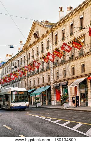 Geneva Switzerland - August 30 2016: Trolley bus on Rue de la Corraterie Street decorated with Swiss flags in the center of Geneva Switzerland. People on the background