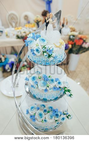 Beautiful three-tiered wedding cake in blue on the wedding Banquet