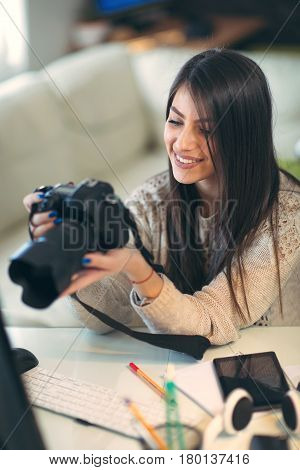 Young photographer looking at her camera at home office