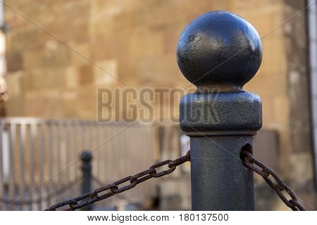 Photo of a bollard with chain and sunlight