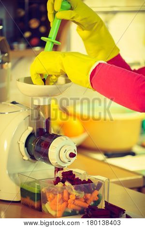 Woman hands adding different vegetables red and green in juicer maker. Housewife in kitchen making raw juice preparing nutritious vitamin packed drink. Healthy eating vegetarian food dieting concept