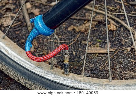 Pumping a bicycle wheel with an old pump