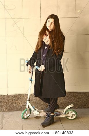 Teenager Sad Girl With Long Brown Hair And Black Coat On Scooter